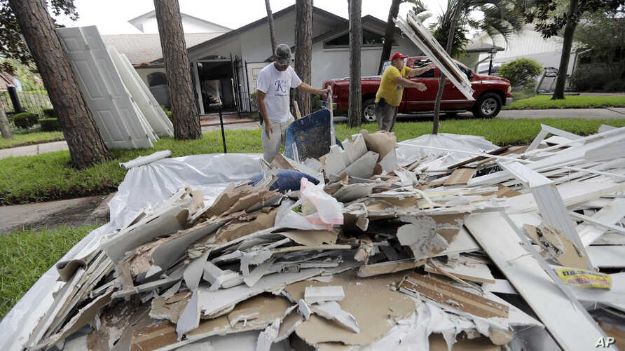 Jose Martinez, left, and William Majano remove drywall and baseboards from a home damaged by floodwaters from Tropical Storm Harvey on Wednesday, Aug. 30, 2017, in Houston.