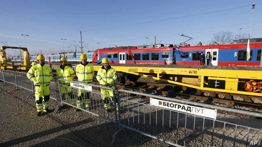 Workers await the ceremony of the reconstruction of a railway line between Budapest and Belgrade, in Belgrade, Serbia, Nov. 28, 2017.