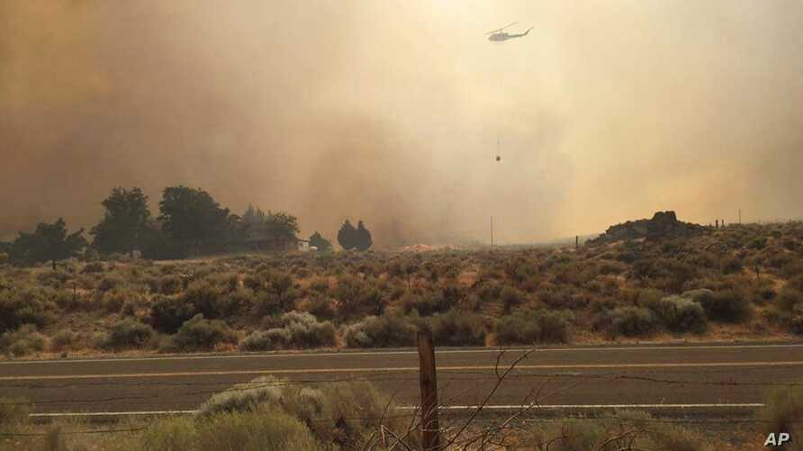 In this photo provided by Vince O'Daye, a helicopter flies over plumes of smoke from a wildfire in the community of Sutcliffe, Nev., about 35 miles north of Reno, Nev.ada, July 30, 2016.
