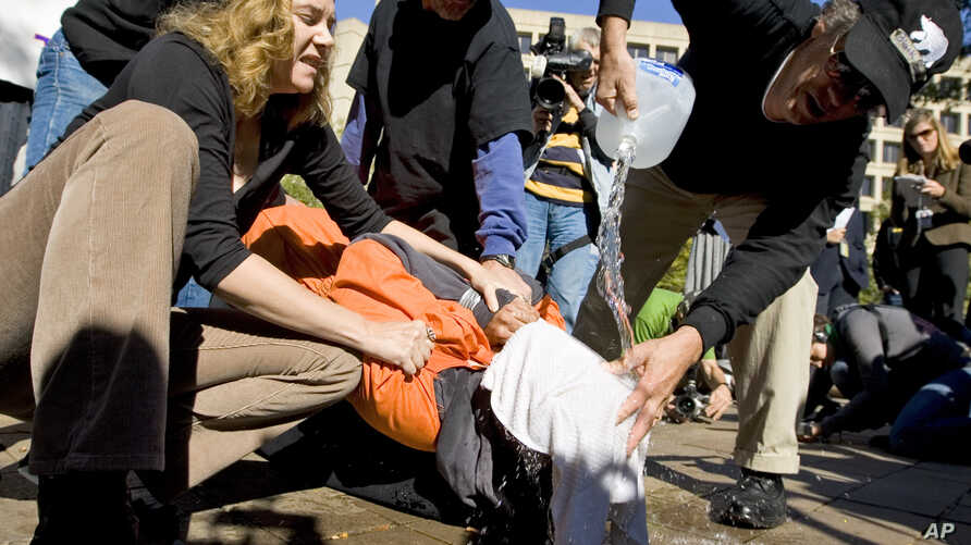FILE - Protestors demonstrate the use of waterboarding in front of the Justice Department in Washington.