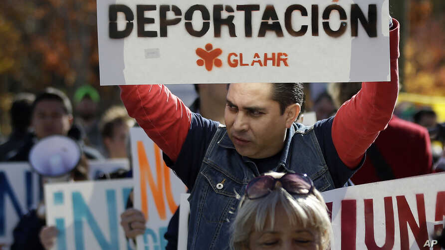 FILE - A man marches with a sign during a protest in front of a building that houses federal immigration offices.