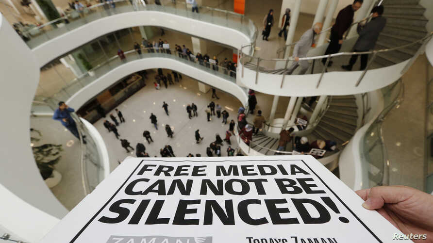FILE - A Zaman journalist holds a banner at the headquarters of Zaman daily newspaper in Istanbul, Dec. 14, 2014.
