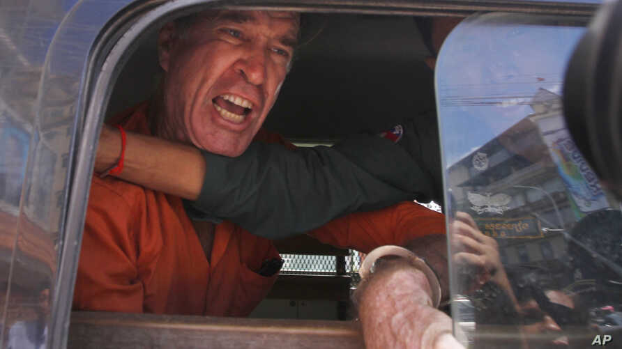Australian filmmaker James Ricketson speaks from a prisoner van outside Phnom Penh Municipal Court, in Phnom Penh, Cambodia, Aug. 31, 2018.