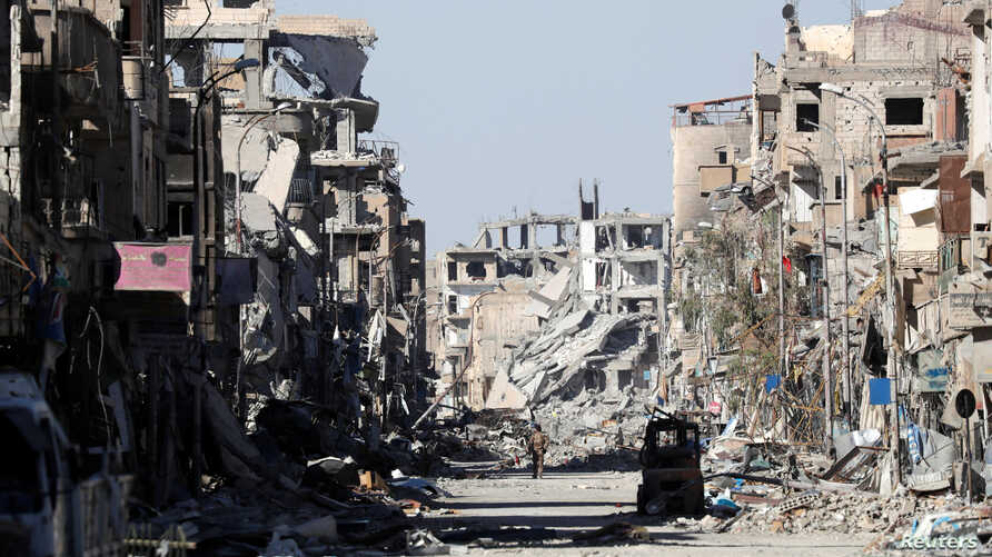FILE - A fighter of the Syrian Democratic Forces stands amid the ruins of buildings near the Clock Square in Raqqa, Syria, Oct. 18, 2017.