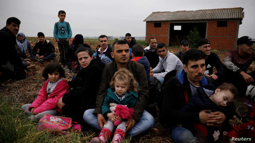 Syrian refugees who crossed the Evros river, the natural border between Greece and Turkey, rest on a field as they wait for the police to arrive and transfer them to a first reception center, near the village of Nea Vyssa, Greece, May 2, 2018.