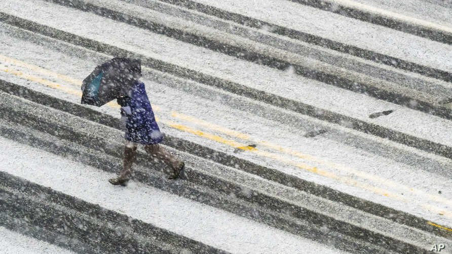 A pedestrian races across the snow-covered and tire-streaked street in Washington during a snow storm, March 21, 2018.