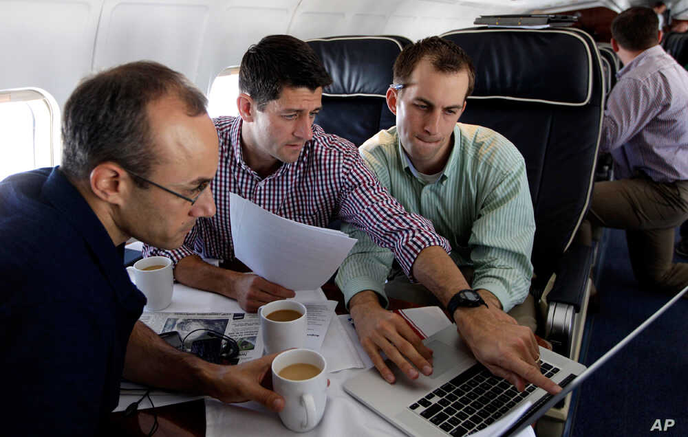 Republican vice presidential candidate, Rep. Paul Ryan, center,  R-Wis., works on the speech he will deliver at the Republican National Convention, with senior adviser Dan Senor, left, and senior aid Conor Sweeney. during the campaign charter flight