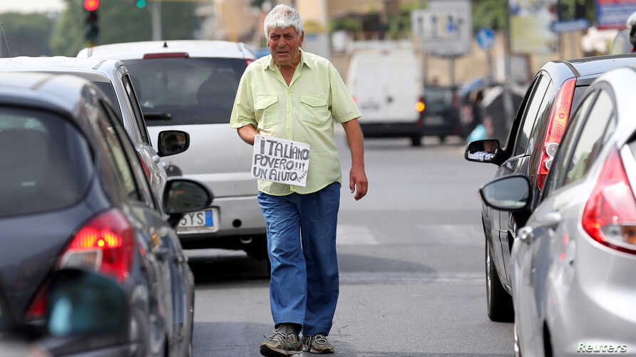 """An Italian man walks between cars as he holds a banner reading """"I'm a poor Italian, help me, thanks"""" in Rome, May 28, 2018."""