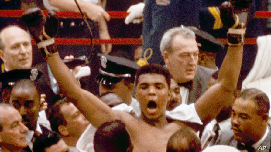 """Muhammad Ali, or Cassius Clay at the time, strikes a familiar pose as he shouts """"I am the greatest,"""" as he leaves the ring, arms raised, following his defeat of former heavyweight boxing champion Sonny Liston in Miami Beach, Fla., February 25, 1964."""