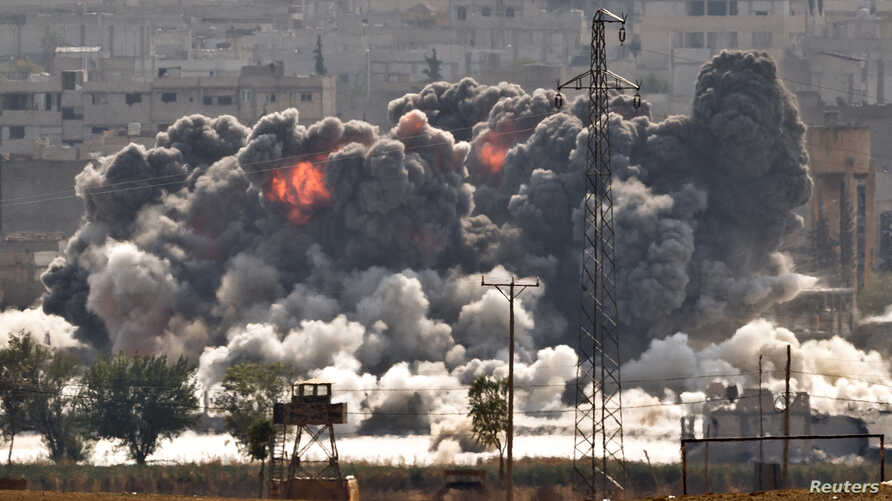 Smoke and flames rise from an Islamic State fighters' position in the town of Kobani during airstrikes by the US led coalition seen from the outskirts of Suruc, near the Turkey-Syria border, Oct. 28, 2014.