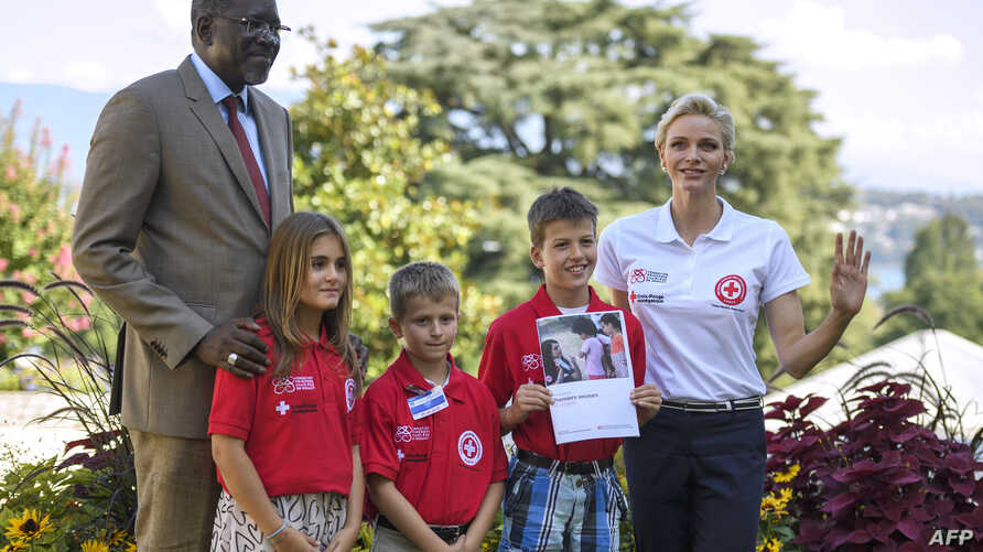 International Federation of Red Cross and Red Crescent Societies (IFRC) goodwill ambassador Princess Charlene of Monaco (R) and IFRC Secretary General Elhadj As Sy (L) pose with children during the launch of World First Aid Day 2016 with this year's