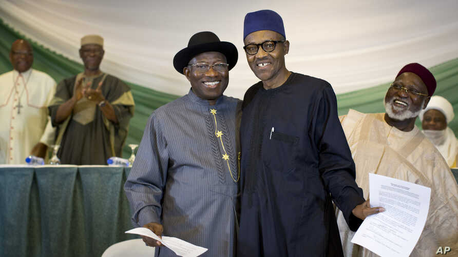 "Nigeria's President Goodluck Jonathan, center-left, and opposition candidate Gen. Muhammadu Buhari, center-right, hug and shake hands after signing a renewal of their pledge to hold peaceful ""free, fair, and credible"" elections, at a hotel in the cap"