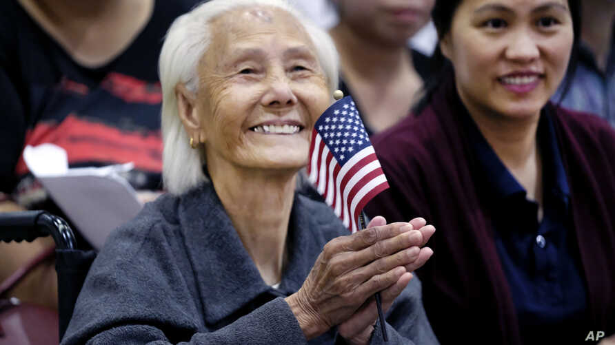 Hong Inh waves an American flag and smiles after taking the oath to become a United States citizen at the Los Angeles Convention Center, in Los Angeles, California, Aug. 22, 2017.