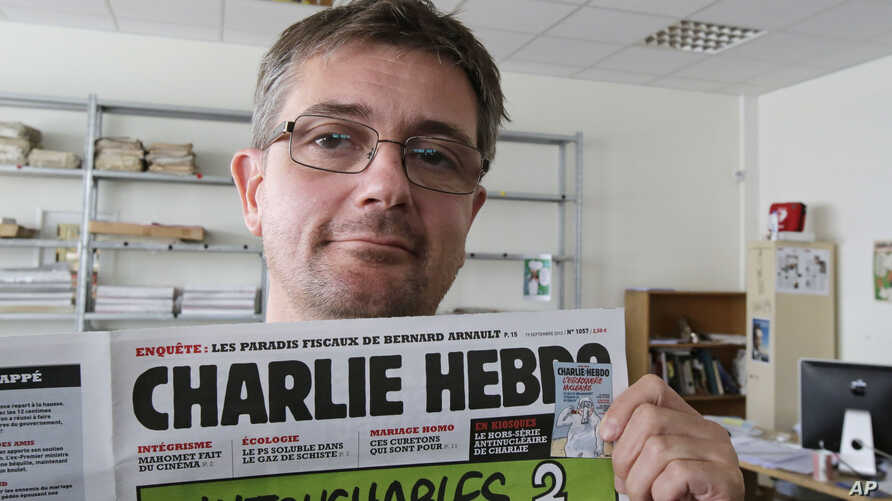 """FILE - Publishing director of the satiric weekly Charlie Hebdo, """"Charb,"""" displays the front page of the newspaper, in Paris, Sept. 19, 2012."""