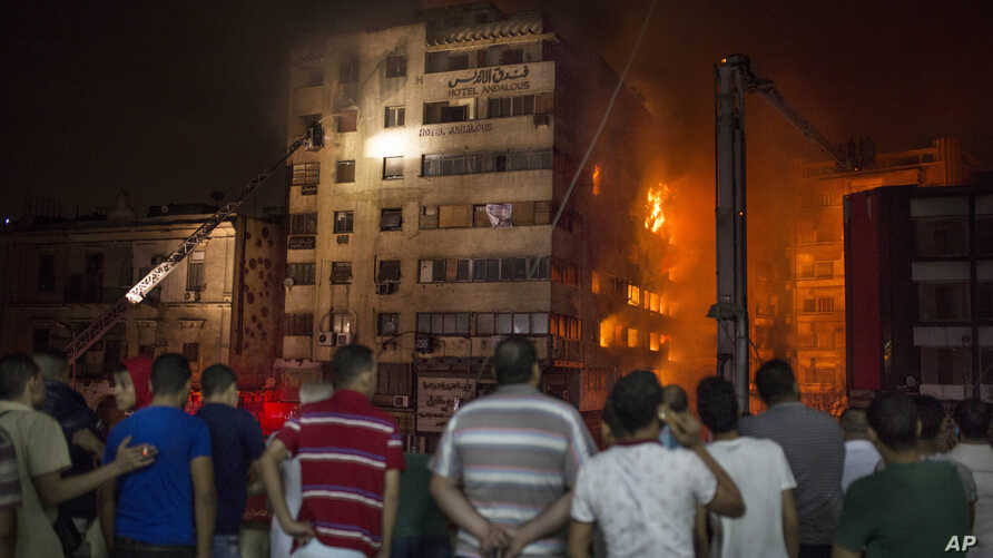 People look at a fire that erupted inside a six-story hotel called Andalusia in the populous Ataba neighborhood in Cairo, Egypt, May 9, 2016.