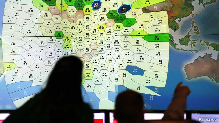 Staff at satellite communications company Inmarsat work in front of a screen at their headquarters in London March 25, 2014.