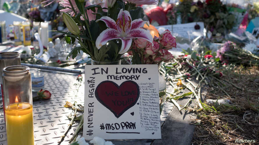 Flowers and mementoes are seen the day students and parents came for voluntary campus orientation at the Marjory Stoneman Douglas High School, Feb. 25, 2018. The school reopens Wednesday, following the Valentine's Day mass shooting in Parkland, Flori