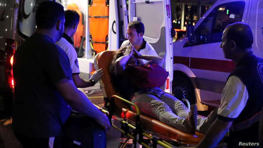 An injured woman covers her face as she is carried by paramedics into ambulance at Istanbul Ataturk Airport, Turkey, following explosions at the facility, June 28, 2016.