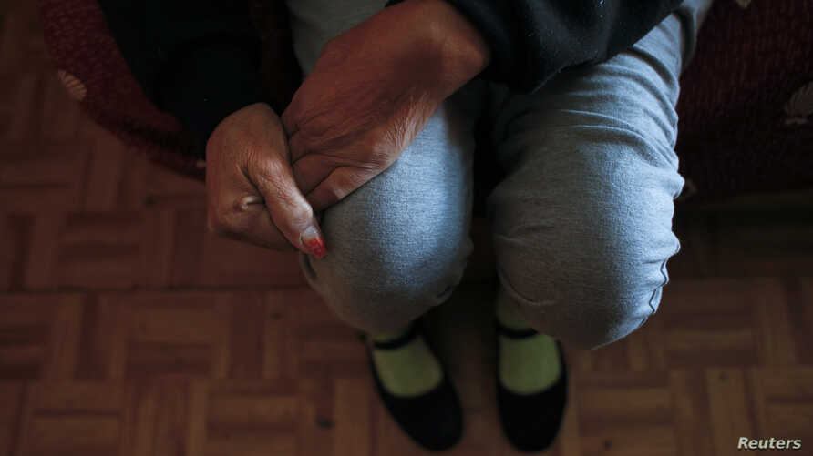 FILE - Susana Reyes sits in her living room. Reyes suffered a thrombosis attack in April 2012 which left her left hand and left leg partially paralyzed.