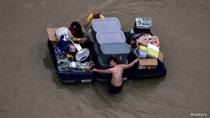 Residents wade with their belongings through flood waters brought by Tropical Storm Harvey in Northwest Houston, Texas,  Aug. 30, 2017.