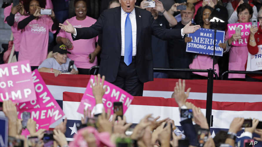 President Donald Trump gestures to supporters as he takes the stage for a campaign rally in Charlotte, North Carolina, Oct. 26, 2018.