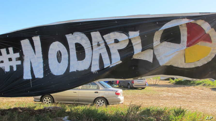 A banner protesting the Dakota Access oil pipeline is displayed at an encampment near North Dakota's Standing Rock Sioux reservation, Sept. 9, 2016.