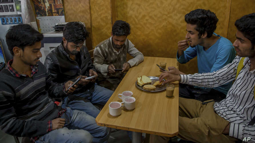 Kashmiri students browse the internet on their mobile phones as they sits inside a restaurant in Srinagar, Indian controlled Kashmir, April 26, 2017. On Wednesday, authorities ordered internet service providers to block 16 social media sites, includ