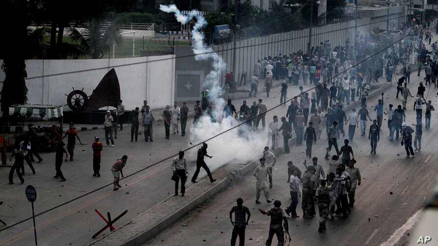 Pakistani protesters hurl back tear gas fired by police, unseen, to stop them from walking toward the U.S. consulate during a demonstration in Karachi, Pakistan, Sunday, Sept. 16, 2012.