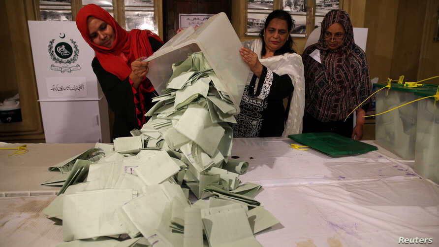 Election officials count ballots after polls closed during the general election in Islamabad, Pakistan, July 25, 2018.