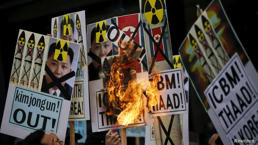 A man burns banners being held by protesters during an anti-North Korea rally in central Seoul, South Korea, Feb. 11, 2016.