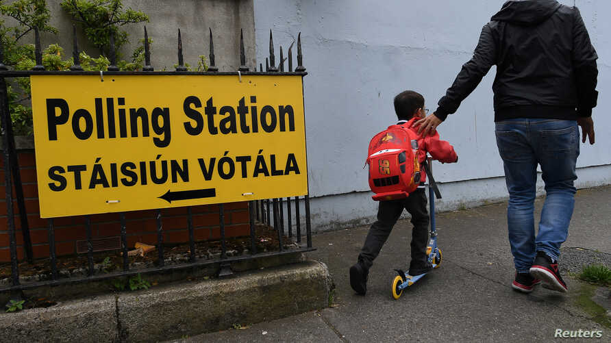 A man and child walk past a sign for a polling station ahead of a 25th May referendum on abortion law, in Dublin, Ireland, May 22, 2018.