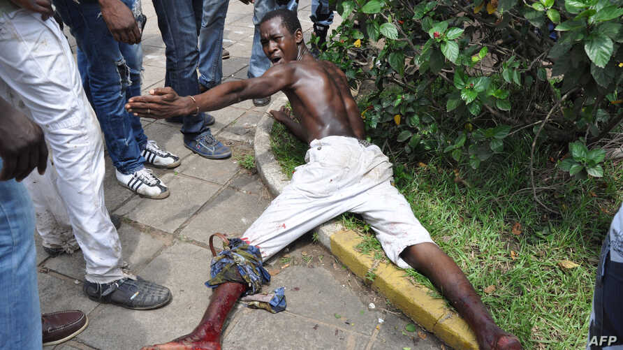 IA injured men lies on the ground after clashed with police at a market in the Abobo neighbourhood in Abidjan, October 15, 2012.