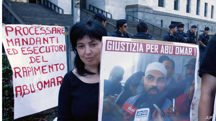 """A protester holding up a poster with writing reading in Italian """"Justice for Abu Omar"""" above a picture of Muslim cleric Osama Moustafa Hassan Nasr, also known as Abu Omar, outside Milan's court house while the trial of 26 Americans and seven Italians"""