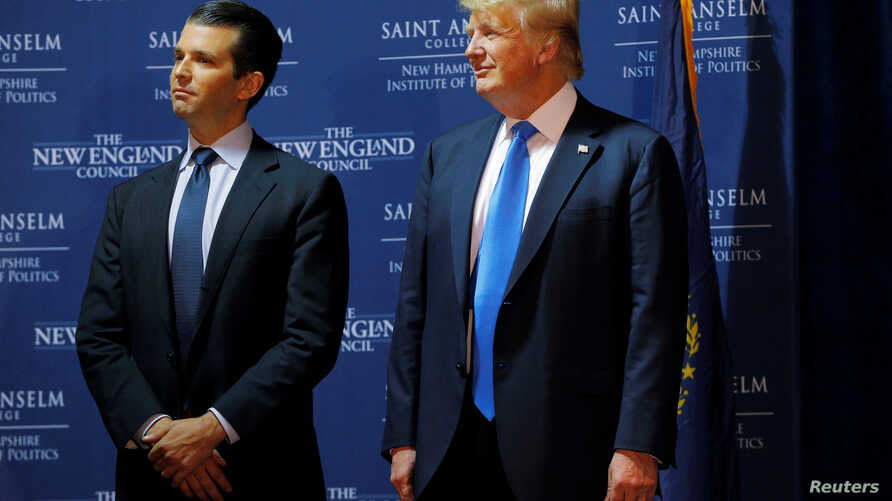 """FILE - Then U.S. Republican presidential candidate Donald Trump welcomes his son Donald Trump Jr. to the stage at one of the New England Council's """"Politics and Eggs' breakfasts in Manchester, New Hampshire, Nov. 11, 2015."""