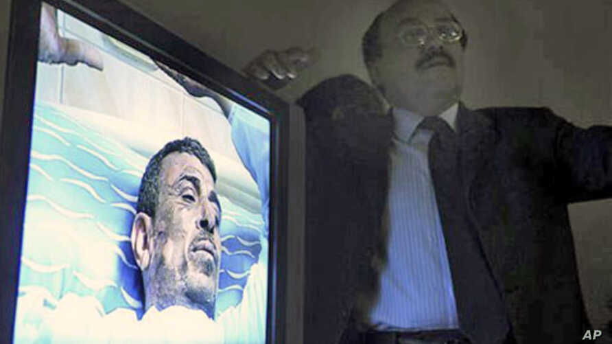 A monitor displays video of 48-year old Abdou Abdel-Monaam Hamadah, at a Cairo hospital, as unidentified plastic surgeon, right, talks about the medical case.  Hamadah apparently set himself on fire Monday outside the country's parliament in a person