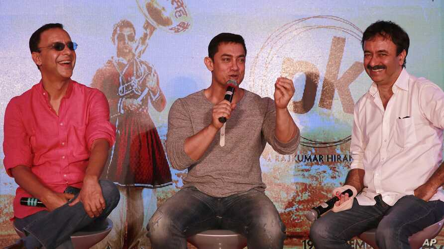 """FILE - Director Rajkumar Hirani, (R), and producer Vidhu Vinod Chopra, (L), enjoy a lighter moment as Bollywood actor Aamir Khan speaks during the unveiling of the second poster of his upcoming film """"PK"""" in Mumbai, India, Aug. 20, 2014."""