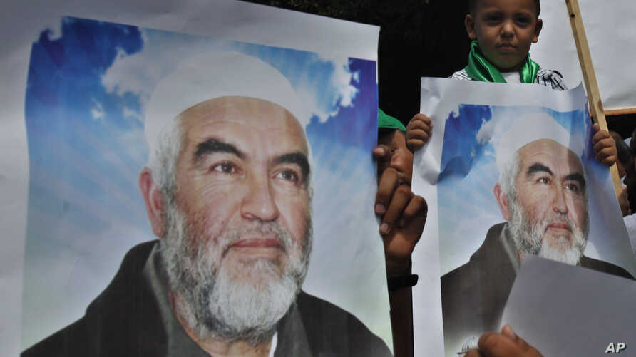FILE - Palestinians in Gaza City carry pictures of Sheik Raed Salah, leader of the Islamic Movement in Israel, during a protest to condemn what protesters claim was a desecration of Al-Aqsa Mosque in Jerusalem by Jewish extremists, Sept. 4, 2013.