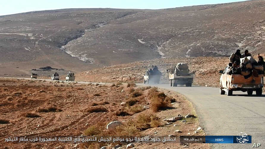 FILE - This image posted online on Saturday, Dec. 10, 2016, by supporters of the Islamic State militant group on an anonymous photo sharing website, purports to show a convoy of vehicles of IS driving in a desert area of east of Palmyra city, in Homs