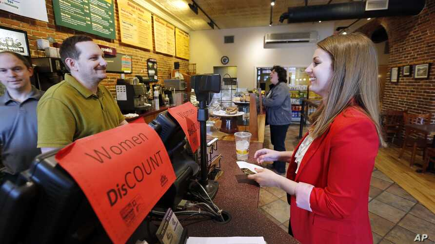 FILE - Molly Kepner, right, smiles after hearing the news of her discount from Tom Grover at The Works Bakery Café in Concord, N.H., April 12, 2016. The New Hampshire bakery chain gave women a break in honor of Equal Pay Day, charging them 79 percent