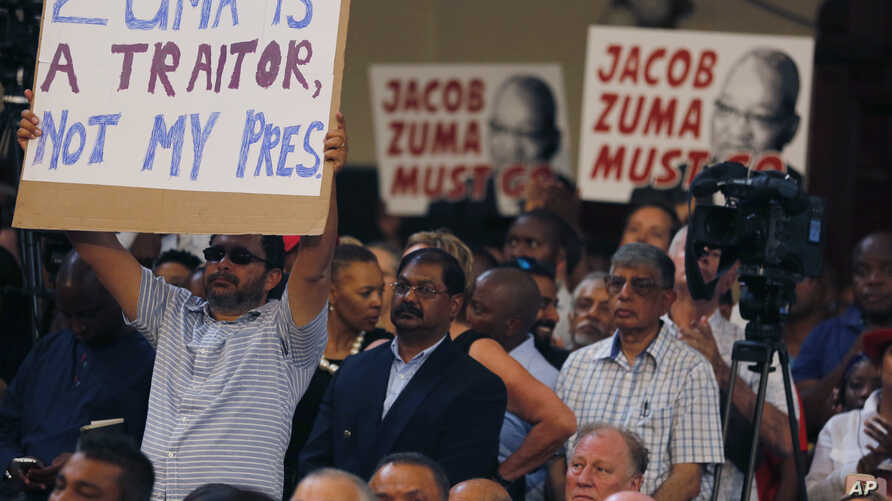 Protesters raise placards against South African President Jacob Zuma in Johannesburg, April 1, 2017, during a memorial service for anti-apartheid stalwart Ahmed Kathrada. The memorial service for Kathrada turned into a protest against Zuma.