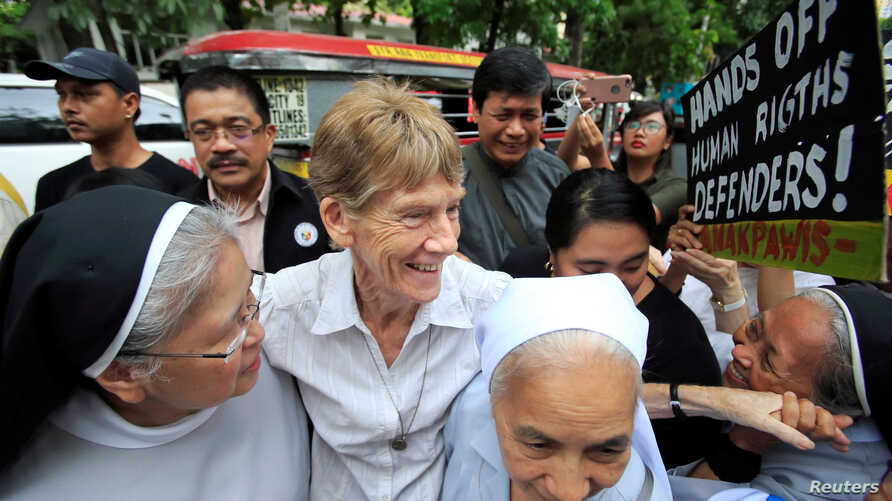 FILE - Australian missionary Patricia Anne Fox, center, is escorted by her colleagues before filing a petition calling for the review of her deportation case at the Department of Justice, in Padre Faura, Manila, Philippines, May 25, 2018. The immigra