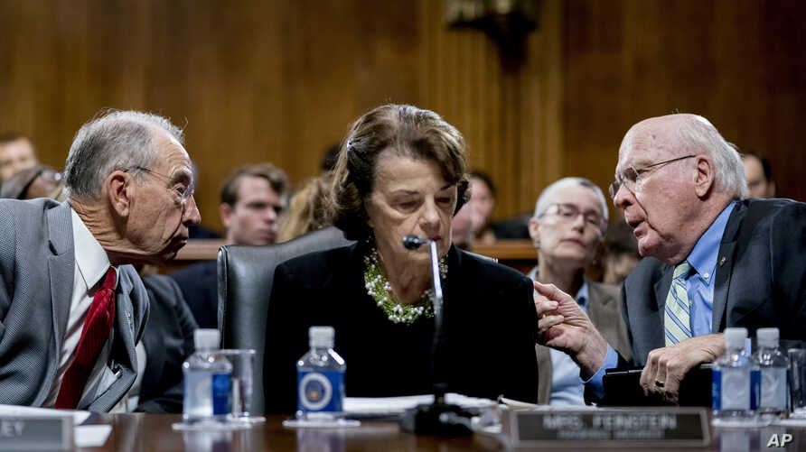 Senate Judiciary Committee Chairman Chuck Grassley, R-Iowa, left, accompanied by Sen. Dianne Feinstein, D-Calif., the ranking member, center, speaks with Sen. Patrick Leahy, D-Vt., right, during a Senate Judiciary Committee markup meeting on Capitol