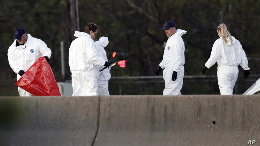 Officials investigate the scene where a suspect in a series of bombing attacks in Austin blew himself up as authorities closed in,  March 21, 2018, in Round Rock, Texas.