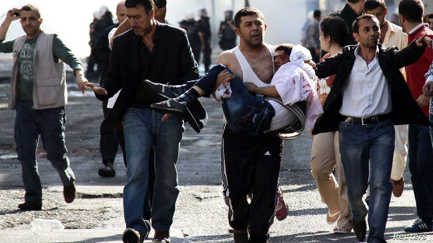 An injured Kurdish protester is carried by his friend as they clash with Turkish riot police in Diyarbakir, Oct. 8, 2014.