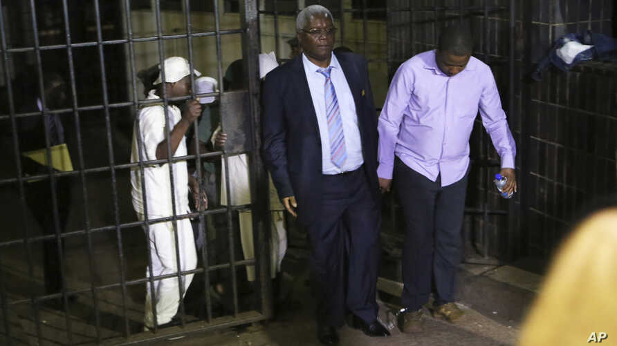 Zimbabwe's former finance minister, Ignatius Chombo, center and Kudzanai Chipanga are led to a prison truck in Harare, Zimbabwe, Nov. 25, 2017. Chombo testified that armed men in masks and uniforms abducted him from his home during the military oper...