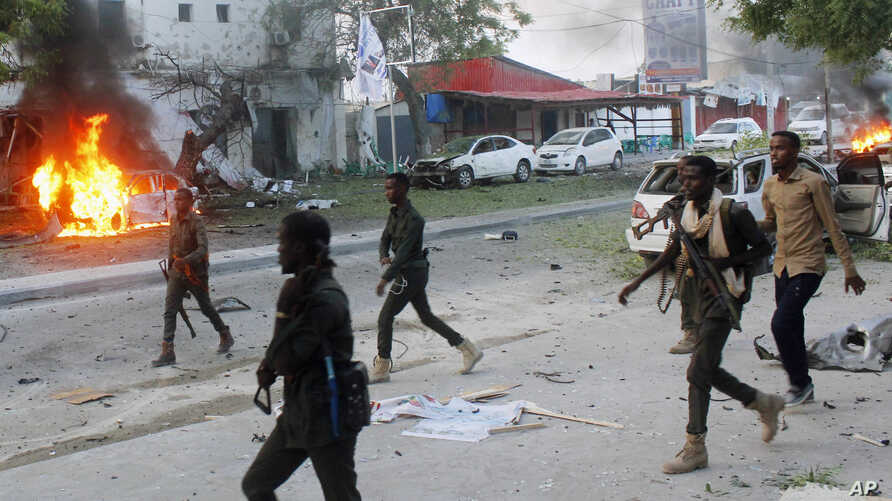 FILE - Security troops walk past burning cars after a fatal car bomb attack on a restaurant in Mogadishu, Somalia, May, 8, 2017. Al-Shabab militants claimed responsibility for the blast. Somalia's states on Sept. 8, 2018, suspended all ties with the