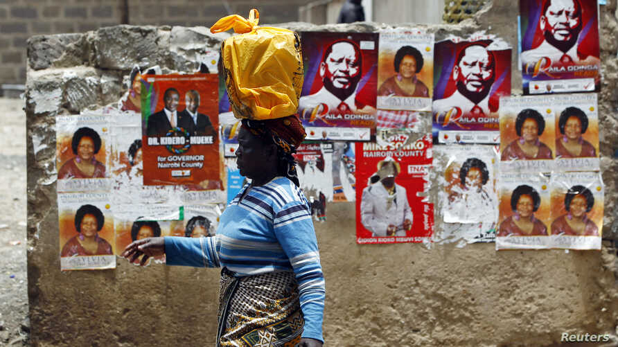 A woman walks past a wall covered with campaign posters on a street in Kenya's capital Nairobi March 3, 2013.
