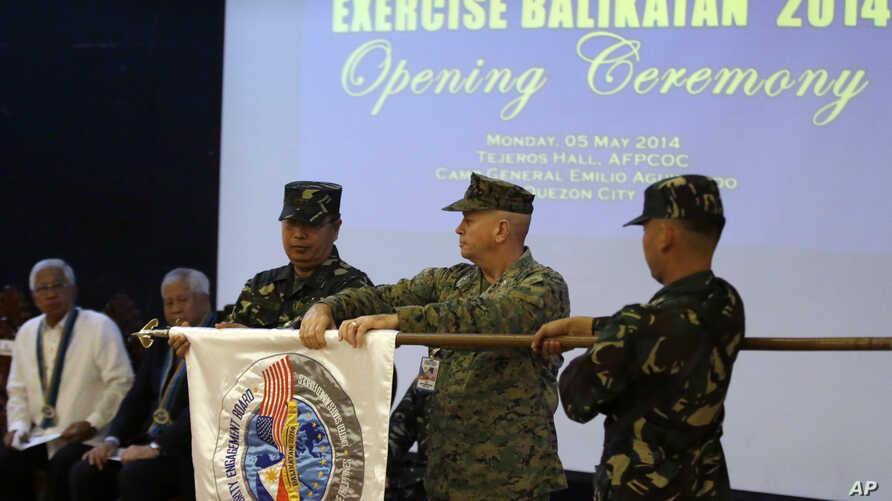 U.S. Marine Col. John Rutherford, second from right, and Philippine Army Maj.Gen. Emeraldo Magnaye, third from right, unfurl the joint U.S.-Philippines military exercise flag during an opening ceremony Armed Forces of the Philippines headquarters in