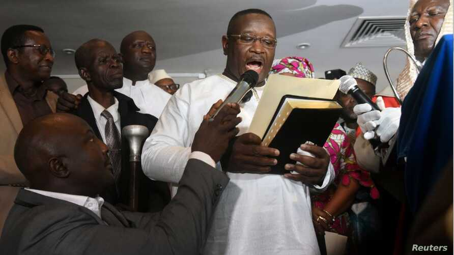 Opposition candidate and former military junta leader Julius Maada Bio takes his oath as Sierra Leone's new president, in Freetown, April 4, 2018.