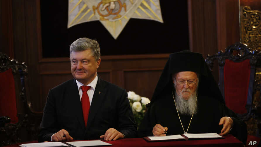 Ukraine's President Petro Poroshenko, left, and Ecumenical Patriarch Bartholomew I sign an agreement following their meeting at the patriarchate in Istanbul, Nov. 3, 2018.